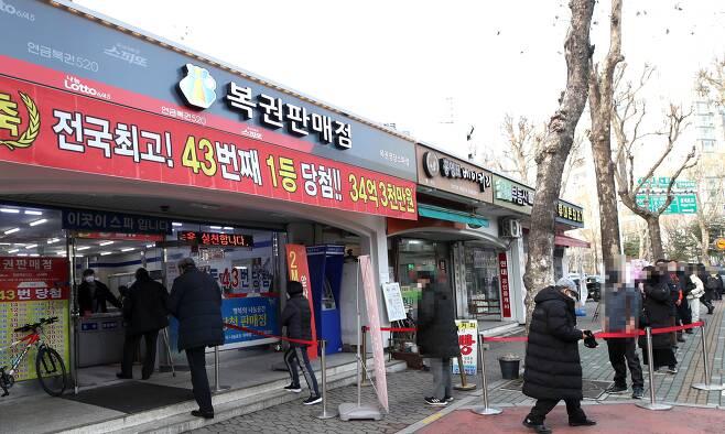 지난 14일 서울의 한 복권 판매점 앞에 로또를 사려는 사람들이 줄 섰다. 지난해 로또 복권의 하루 평균 판매액은 130억원(잠정치)으로 역대 최고치를 기록했다. /뉴시스