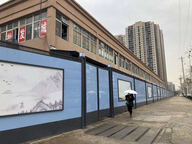 21일 중국 후베이성 우한시 도심의 옛 화난 수산시장이 높은 벽으로 둘러싸여 있다 / 사진 출처 : 연합뉴스