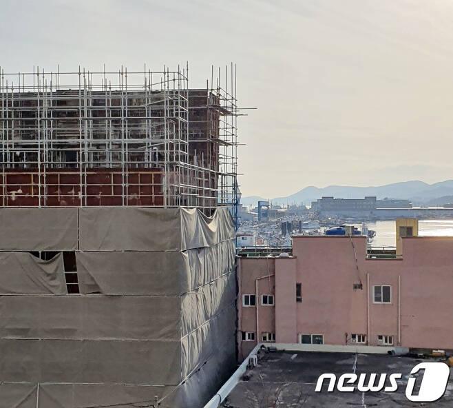 전남 목포 죽교동 지구단위계획 구역에 증축되고 있는 3층짜리 건물(왼쪽)과 일반적인 기준의 3층짜리 상가 건물(오른쪽). 바다가 보이는 오른쪽 건물과는 달리 신축 건물은 바다를 모두 가려 보이지 않는다.(독자제공)2021.1.24/뉴스1 © News1