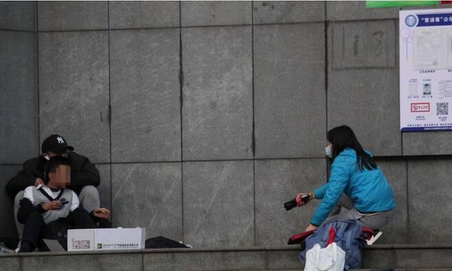 지난 22일 '윈난 TV라디오' 기자라고 밝힌 여성(오른쪽)이 중학생을 인질로 잡고 있는 흉악범과 인터뷰를 시도하고 있다. /글로벌타임스
