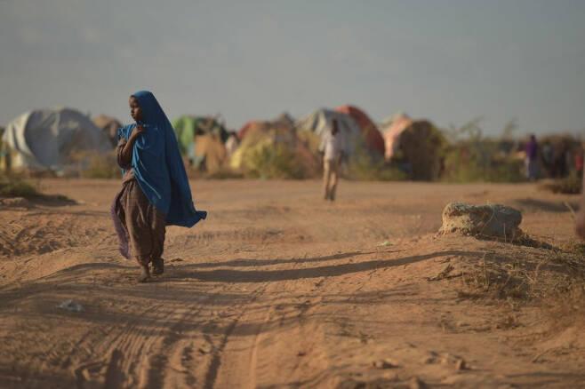 소말리아 도시 벨레트웨인에서 한 소녀가 '내부 유민' 캠프 주변을 걷고 있다. 소말리아는 만성적인 가뭄 등 기후변화로 인한 소득감소로 농민들이 자국 내 대도시 주변으로 몰려들어 '내부 유민'이 되거나 아예 케냐 등 인근 국가로 떠나는 난민이 되고 있다.  더뉴휴머니태리언 제공