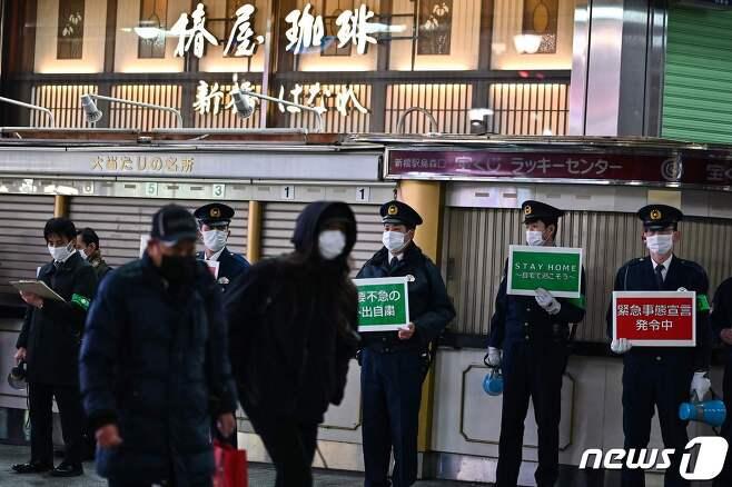일본 도쿄 시내 길거리에서 경찰들이 외출 자제를 당부하는 팻말을 들고 서 있다. © AFP=뉴스1