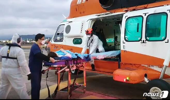 26일 제주대병원 관계자와 소방대원들이 조기출산 위험에 처한 임신부를 소방헬기로 이송하고 있다.(제주소방안전본부 제공)2021.1.27 /뉴스1© News1