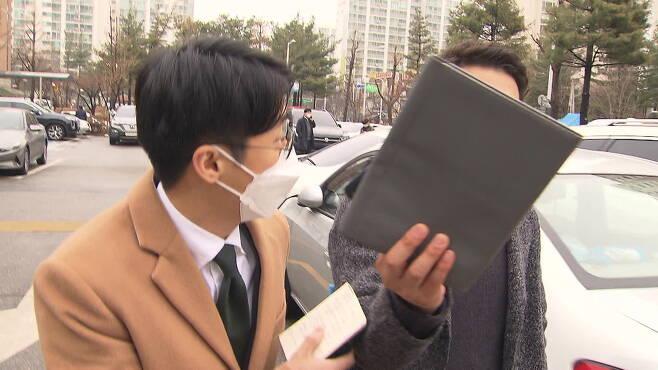 지난달 22일 임금 체불 진정 사건으로 고용노동부 부천지청에 출석한 회사 대표가 취재진의 카메라를 가리고 있다.