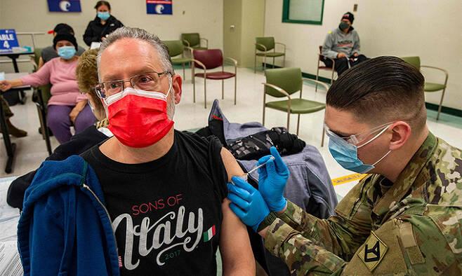 미국 매사추세츠주 이스트 보스턴의 한 신종 코로나바이러스 감염증(코로나19) 백신 접종소에 배치된 주 방위군 병사가 지난 16일(현지시간) 한 주민에게 백신을 접종하고 있다. 이스트 보스턴=AFP연합뉴스