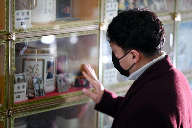 업무상 질병으로 인한 자살 산재 승인을 받은 고(故) 손원경(가명)씨의 형이 지난 18일 경기 이천시 추모의집에서 동생의 사진을 어루만지고 있다. 이천=윤성호 기자