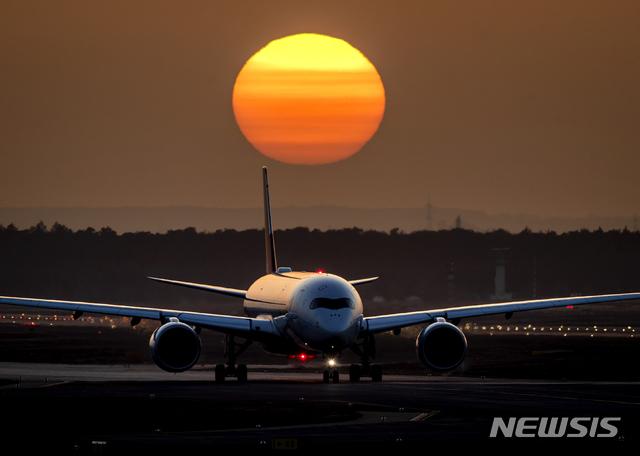 [프랑크푸르트=AP/뉴시스] 2월23일(현지시간) 독일 프랑크푸르트 공항에 해가 지는 가운데 항공기 한 대가 이륙하기 위해 활주로를 이동하고 있다. 2021.02.24.