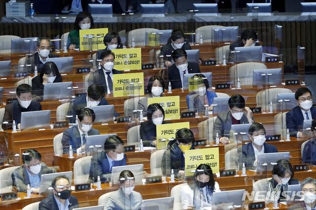 [서울=뉴시스]최동준 기자 = 정의당 의원들이 26일 서울 여의도 국회 본회의에서 가덕도 관련 법안을 비판하는 피켓을 의석에 붙여 놓고 있다. 2021.02.26. photocdj@newsis.com