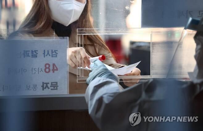코로나19 신규확진 415명 지난 27일 오전 서울역에 설치된 임시선별진료소에서 한 시민이 코로나19 검사를 받은 후 검체를 제출하고 있다. [연합뉴스 자료사진]