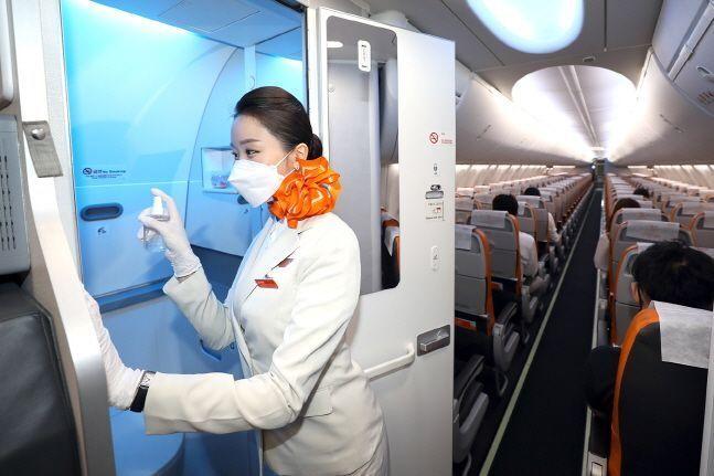 제주항공 한 승부원이 기내에서 소독 스프레이를 이용해 기내 화장실 내부 및 화장실 손잡이 소독을 실시하고 있다.(자료사진)ⓒ제주항공