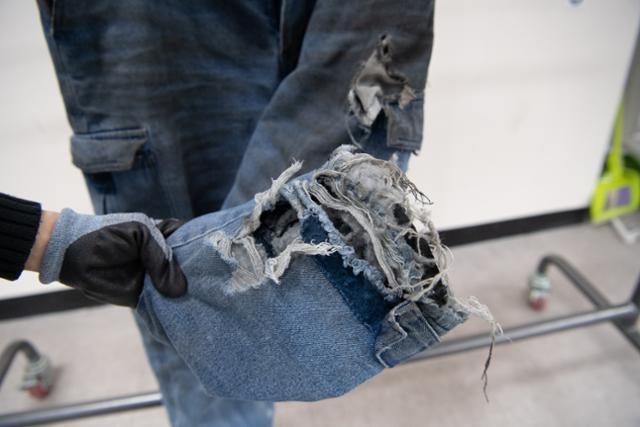 한 작업복의 밑단이 심하게 해져 있다.