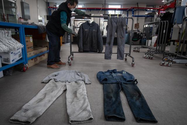 김해 노동자 작업복 세탁소 '김해클리닝'의 한 직원이 세탁 작업에 앞서 노동자들이 맡긴 작업복들의 상태를 꼼꼼하게 점검하고 있다. 이 세탁소에서 일하는 자활 직원들 역시 한때는 현장에서 일하던 노동자였다.