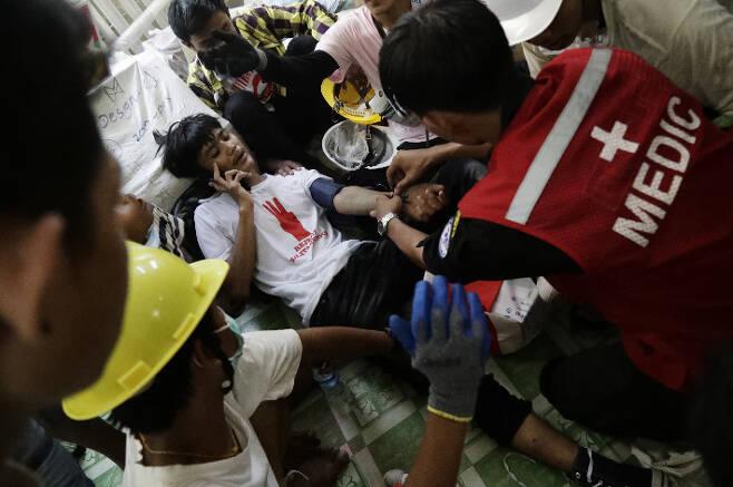 3일(현지시간) 미얀마 최대 도시 양곤의 쿠데타 반대 시위 현장에서 의료진이 부상자를 치료하고 있다. 연합뉴스