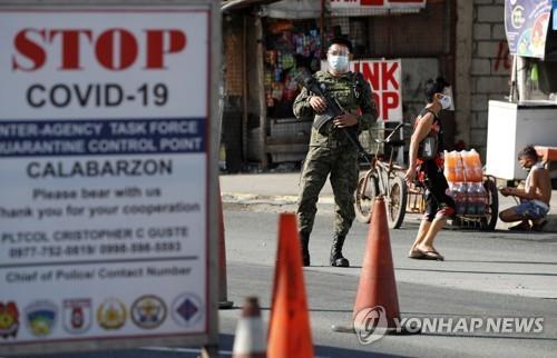 필리핀 경찰이 메트로 마닐라 인근 검문소에서 경계를 서고 있다. 2021.3.22 [EPA=연합뉴스]