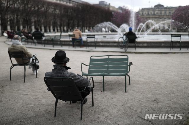 [AP/뉴시스] 3월22일 프랑스 파리의 팔레 르와이알 정원에서 시민들이 띄엄띄엄 의자에 앉아 분수를 바라보고 있다. 파리 등 10여 개 현이 주말 록다운을 추가 실시하고 있다.