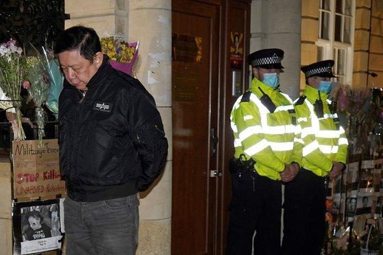 영국 주재 미얀마 대사인 쪼 츠와 민(왼쪽 끝)이 지난 7일(현지시간)밤 런던에 위치한 미얀마 대사관 앞을 서성이고 있다. [AFP=연합뉴스]