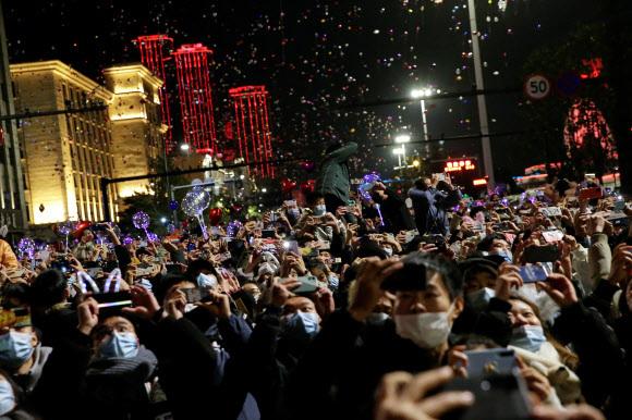 코로나19 감염병의 진원지인 중국 우한 시민들이 31일 새해 전야 행사에 운집해 있다. 마스크를 쓰긴 했지만 한국이 5명 이상 모이지 않게 하는 등 강력한 사회적 거리 두기를 시행하는 것과 대조를 이룬다.우한 로이터 연합뉴스