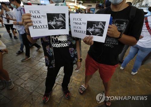 쿠데타 이후 태국에 사는 미얀마인들이 쁘라윳 태국 총리와 흘라잉 미얀마군 최고사령관을 나란히 담은 인쇄물을 들고 두 사람을 비판하는 시위를 벌이고 있다. 2021.2.28  [EPA=연합뉴스]