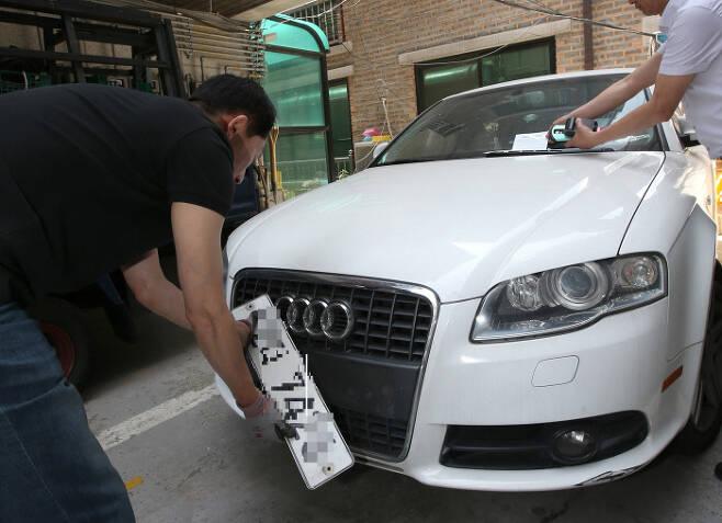 구청 세무관리과 직원들이 자동차세 등 차량 관련 과태료 체납액이 많은 차량의 번호판을 영치하는 모습. 기사와 관련없음. 연합뉴스
