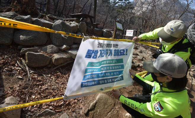 등산로 곳곳에 설치된 코로나19 탐방 거리두기 안내문을 점검하는 대원들.