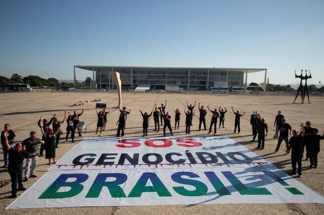 브라질 정부의 코로나19 대책에 반감을 가진 시민들이 브라질 수도 브라질리아에서 지난주 '브라질에서 학살이 벌어지고 있다'는 내용의 SOS 메시지를 전달하는 시위를 하고 있다.[EPA]
