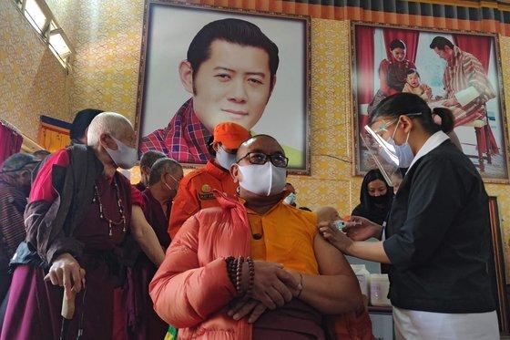 지난달 27일 부탄에서 한 남성이 코로나19 백신을 맞고 있다. 벽에 걸린 초상화 속 인물은 발빠른 백신 리더십으로 호평을 받고 있는 지그메 케사르 남기엘 왕추크 국왕. [AFP=연합뉴스]