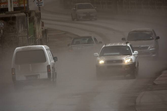 화산재가 눈처럼 쏟아진 도로를 달리는 자동차들. 사진=AP 연합뉴스