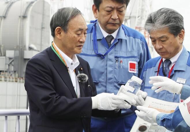 """정화한 오염수 받은 스가…마시지는 않았다. (후쿠시마 교도=연합뉴스) 스가 요시히데(菅義偉) 일본 총리가 2020년 9월 26일 일본 후쿠시마(福島) 제1원전에서 정화처리한 방사성 물질 오염수가 든 용기를 들고 있다. 스가 총리는 당시 다핵종(多核種)제거설비(ALPS)로 거른 오염수를 """"희석하면 마실 수 있다""""는 설명을 듣고 """"마셔도 되냐""""고 물었으나 실제로 마시지는 않았다."""