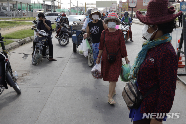 [프놈펜=AP/뉴시스] 2일 캄보디아 수도 외곽 마을에서 사람들이 음식물을 사고 서둘러 집으로 가고 있다. 수도 일부 구역은 통행이 폐쇄돼 온라인 배달만 가능하다