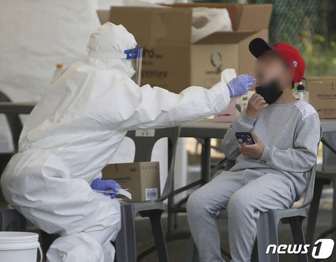 울산지역에 신종 코로나바이러스 감염증(코로나19) 변이 바이러스 확산세가 이어지고 있는 5일 울산 남구 문수축구경기장에 마련된 임시 선별검사소에서 한 학생이 검사를 받고 있다. 2021.5.5/뉴스1 © News1 윤일지 기자
