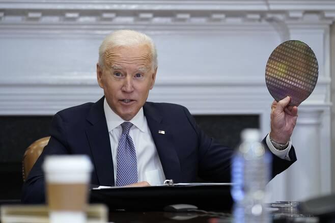 조 바이든 미국 대통령이 4월 12일(현지시간) 백악관 루즈벨트룸에서 반도체 업계 대표들과 화상 회의를 진행하는 도중 실리콘 웨이퍼를 꺼내들고 있다/AP 연합뉴스