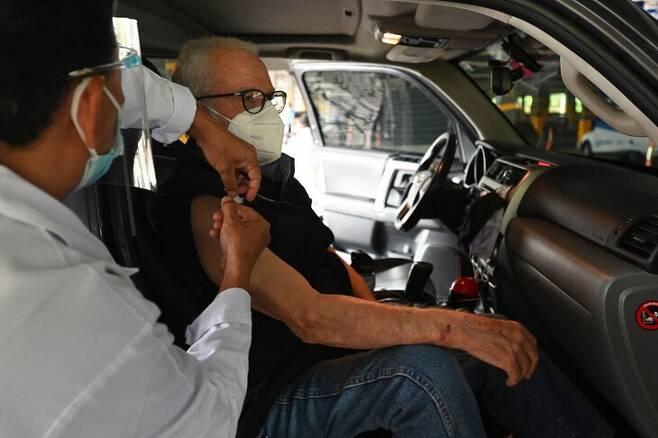 중남미 과테말라의 과테말라시에서 한 노인이 차 안에 탄 채 코로나19 백신을 맞고 있다. 과테말라/AFP 연합뉴스