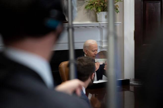 지난달 12일 바이든 대통령이 삼성전자 등 반도체 대기업을 초청해 화상회의를 열고 반도체 웨이퍼를 들어 보이고 있다(사진=AFP)