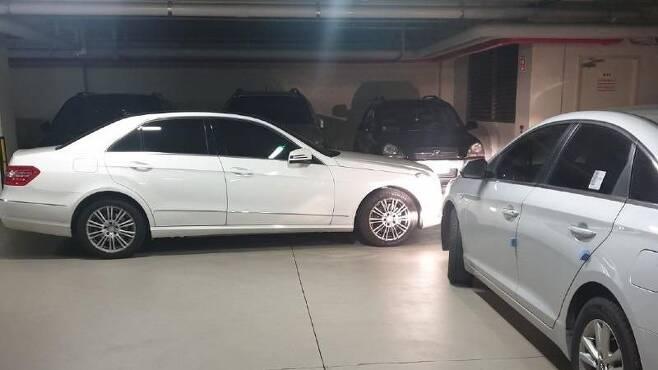한 아파트 지하주차장에 흰색 벤츠 차량이 다른 차들 통행을 막으면서 이중으로 주차돼 있다. /보배드림