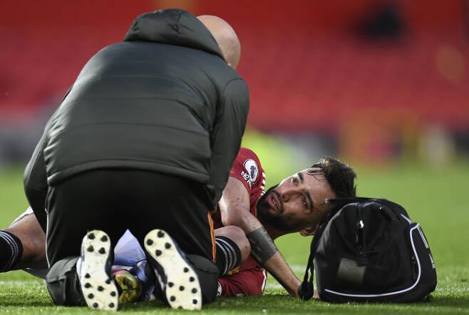 맨유 브루노 페르난데스가 14일 리버풀전에서 상대 태클로 넘어진 뒤 의료진의 치료를 받고 있다. AP연합뉴스