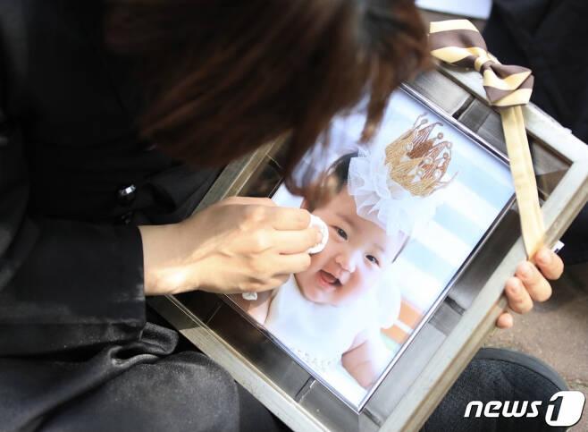 16개월 된 입양아 정인양을 학대해 숨지게 한 혐의를 받는 양부모의 1심 선고공판이 열린 14일 오후 양천구 서울남부지방법원 앞에서 상복을 입은 한 시민이 정인이 사진을 닦고 있다.사진=뉴스1