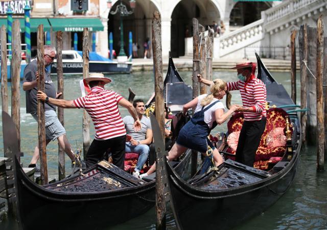 이탈리아의 베네치아가 코로나19 확산 위험이 낮은 '화이트존'으로 분류되면서 제한조치가 완화된 7일 곤돌라 뱃사공들이 여행객들의 탑승을 돕고 있다. 베네치아=로이터 연합뉴스