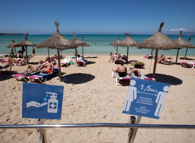 7일 스페인 팔마 데 마요르카의 팔마해변을 찾은 관광객들이 일광욕을 즐기고 있다. 스페인은 7일부터 세계보건기구(WHO)나 유럽의약품청이 승인한 코로나19 백신 접종자를 대상으로 외국인 관광객들에게 국경을 개방했다. 팔마 데 마요르카=AFP 연합뉴스