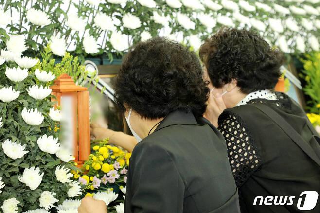 11일 오전 광주 붕괴 사고 희생자들의 합동분향소가 차려진 광주 동구청 앞 분향소에서 희생자 친구들이 영정사진을 만지며 오열하고 있다.2021.6.11/뉴스1 © News1 허단비 기자
