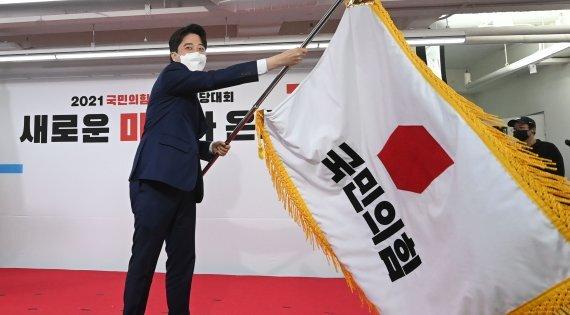 이준석 국민의힘 신임 대표가 11일 오전 서울 영등포구 당사에서 열린 전당대회에서 당기를 흔들고 있다. '30대·0선'의 이 대표는 헌정사상 최초의 30대 보수정당 대표에 올랐다. /사진=뉴스1