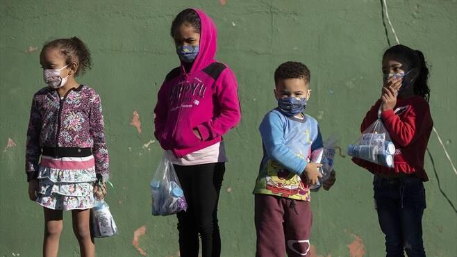 백신 집단면역, 성인 접종만으로도 가능할까 - 브라질 상파울로 시내에서 아이들이 마스크와 위생용품을 들고 밖에 나와있는 모습.네이처 제공
