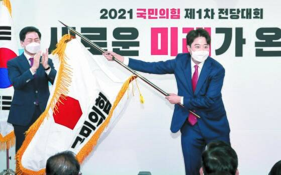 """11일 열린 국민의힘 전당대회에서 이준석 대표가 김기현 원내대표로부터 전달받은 당기를 흔들고 있다. 4일간 진행된 경선에서 9만3392표(43.8%)를 얻어 새 당대표로 선출된 그는 """"다양한 대선주자와 지지자들이 공존할 수 있는 당을 만들 것""""이라고 밝혔다. 오종택 기자"""
