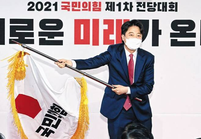 지난 11일 서울 여의도 중앙당사에서 열린 전당대회에서 이준석 새 대표가 국민의힘 당기를 흔들고 있다. /연합뉴스