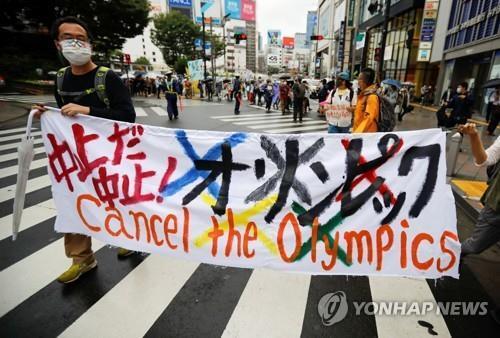 (도쿄 로이터=연합뉴스) 19일 일본 도쿄도(東京都)에서 올림픽 취소를 요구하는 시민이 횡단막을 들고 시위를 하고 있다.