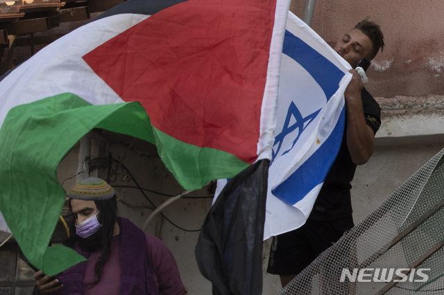 [예루살렘= AP/뉴시스] 예루살렘 구시가지에 있는 팔레스타인 사람들의 집이 4월 16일 이스라엘인들에게 강제로 점령당한 뒤 양쪽 시위대가  깃발을 들고 나와 대치하고 있는 모습. 예루살렘에서는 라마단이 시작된 이후 팔레스타인인 집회를 막는 경찰과 시위대의 충돌이 매일 밤 벌어지고 있다.