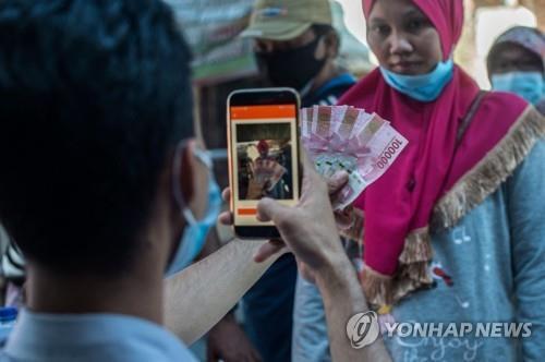 코로나 정부 지원금 받고 인증샷 찍는 수마트라 시민 [AFP=연합뉴스]