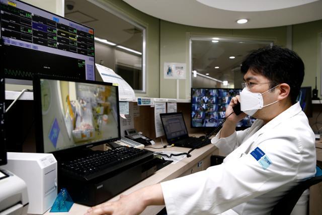 21일 경기 고양시 국민건강보험공단 일산병원에서 최흔 일산병원 감염내과 교수가 격리 병실에서 치료받고 있는 코로나19 환자의 상태를 전화로 확인하고 있다. 일산병원 제공