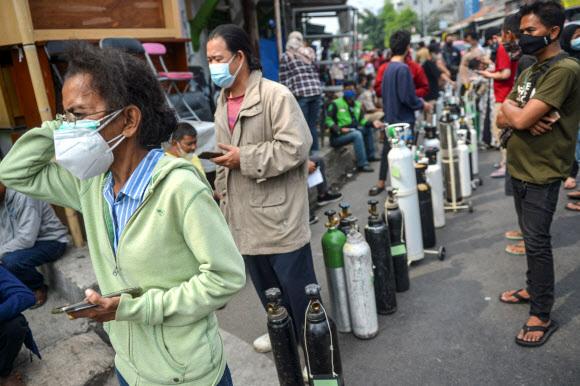 자카르타의 코로나바이러스 질환자 급증 - 2021년 7월 15일 인도네시아 자카르타에서 코로나19 환자가 급증하는 가운데 마스크를 쓴 사람들이 산소통을 들고 서서 무료로 보충하고 있다. 로이터 연합뉴스 2021-07-15