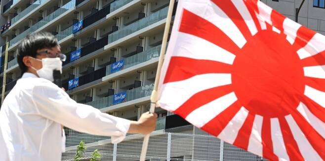 ▲ 일본 극우단체 관계자가 선수촌 앞에서 욱일기를 들고 시위하고 있다. ⓒ연합뉴스