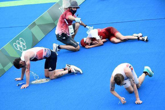26일 오전 열린 도쿄올림픽 트라이애슬론 경기에서 레이스를 마친 선수들이 바닥에 쓰러져 구토하는 등 고통스러워하는 모습. AFP 연합